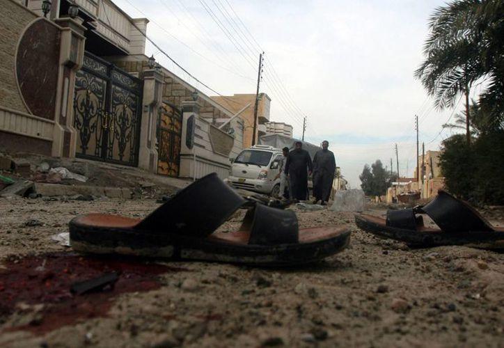 Un grupo de hombres camina por el lugar donde dos civiles murieron y otros cuatro resultaron heridos en Faluya, a 50 kilómetros de Bagdad. (Archivo/EFE)
