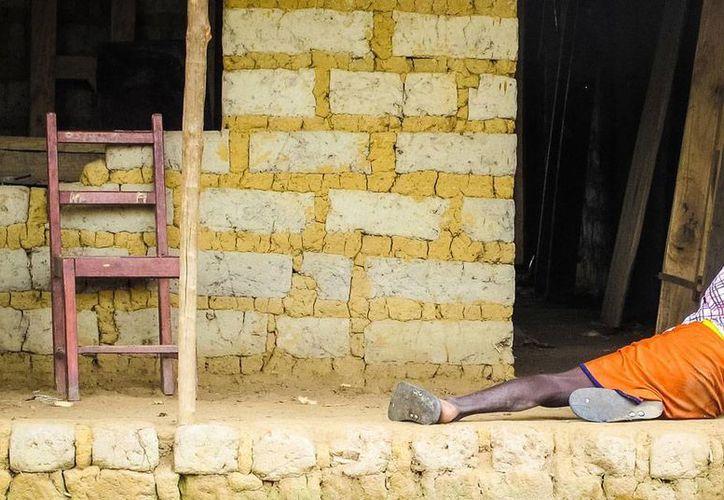 Muchos enfermos de ébola, como el que puede verse parcialmente en la foto, mueren a las puertas de sus casas, sin ninguna asistencia médica. La foto es de un sitio de Sierra Leona, en África. Según la OMS, más de 4,800 personas han muerto por la enfermedad. (AP)