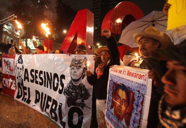 Manifestantes participan en la marcha del silencio con antorchas y velas anoche, en Ciudad de México, en donde recordaron a las víctimas de los disturbios de Nochixtlán. (EFE)