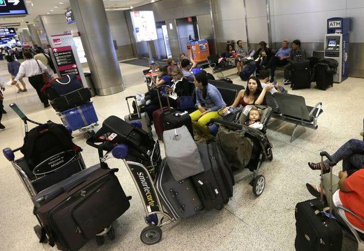 Viajeros aguardan a que se reanuden los vuelos en el Aeropuerto Internacional de Miami, Florida, el 25 de noviembre de 2014. (Foto: AP)