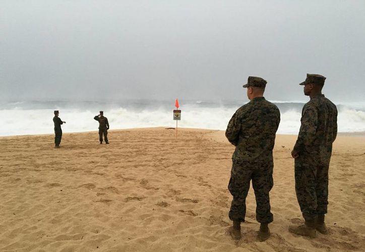 Dos marines de EU caminan sobre la playa de la bahía Waimea cerca de Haleiwa, Hawaii, en donde dos helicópteros de la Infantería de Marina chocaron frente a la isla hawaiana de Oahu. Se lleva a cabo una operación de búsqueda, informaron oficiales militares. (Mariana Keller vía Foto AP)