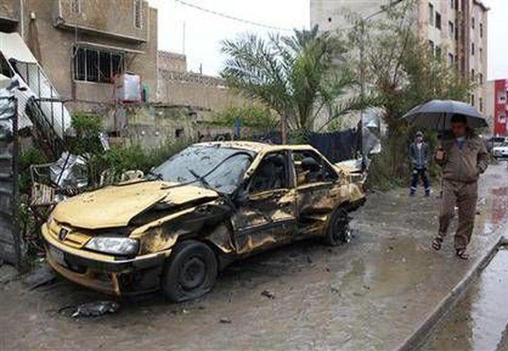 Un vehículo dañado por un coche bomba en una zona comercial del barrio de Hurriyah, en Bagdad, Irak, el lunes 3 de febrero de 2014. (AP/Hadi Mizban)
