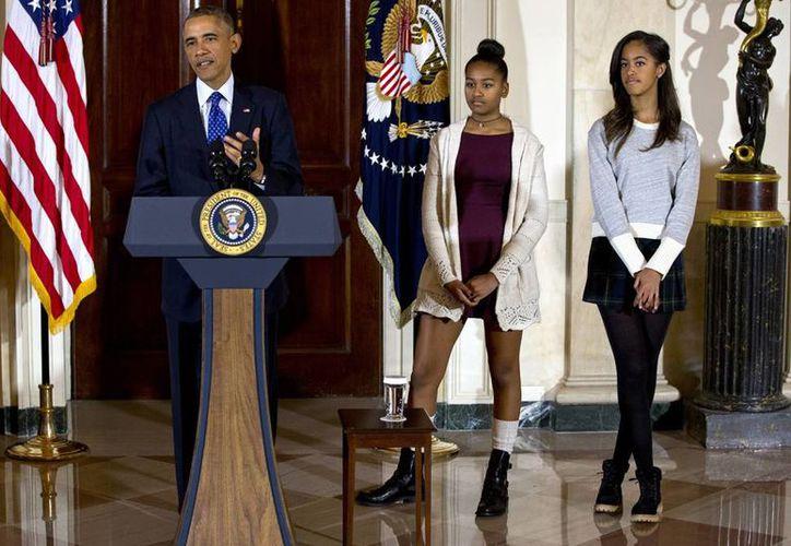 Imagen del presidente Barack Obama junto a sus hijas Malia (derecha) y Sasha, en la Casa Blanca durante la tradicional ceremonia de Acción de Gracias en que el mandatario le perdona la vida a un pavo. (Agencias)
