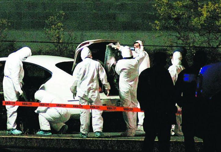 Peritos de Nuevo León levantan los cuerpos de los hermanos Balmori Garza el domingo pasado. (Milenio)