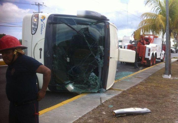 El chofer del autobús no pudo controlar la unidad y se volcó en el camellón de la avenida Tulum. (Redacción/SIPSE)