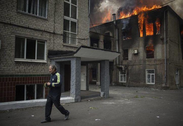 Un hombre camina junto a la comisaría en llamas de Mariupol (Ucrania) este viernes. (EFE/Archivo)