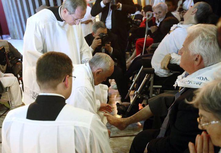 El Papa lava los pies de ancianos, incapacitados, mujeres, no católicos, en la Fundación Don Gnocchi en Roma, durante el ritual del Jueves Santo. (AP Foto/Riccardo De Luca)
