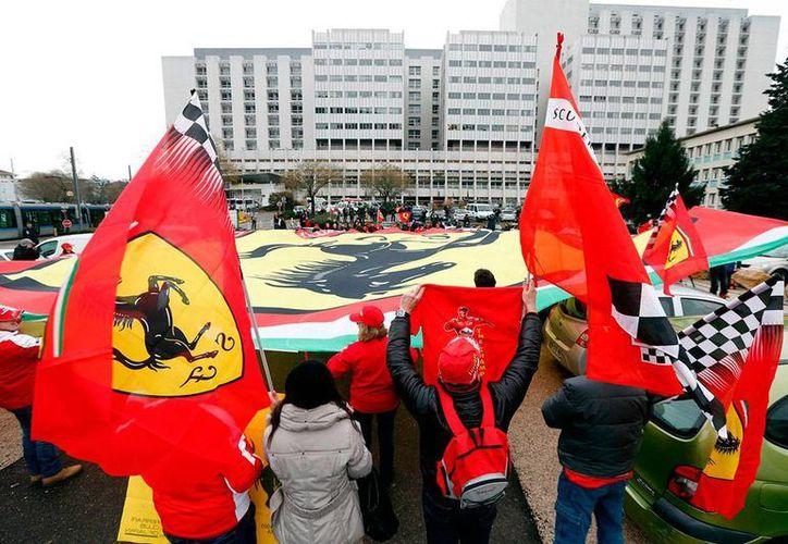 Aunque el piloto alemán Michael Schumacher permanece en la Grenoble, ya no está en terapia intensiva. Imagen de archivo de seguidores del corredor, a las afueras del hospital, en Francia. (excelsior.com.mx)