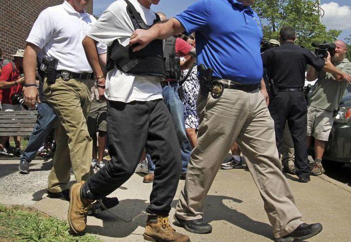 El sospechoso del tiroteo de Charleston, Carolina del Sur, Dylann Storm Roof, con chaleco antibalas, es escoltado por policías tras su arresto. (Agencias)