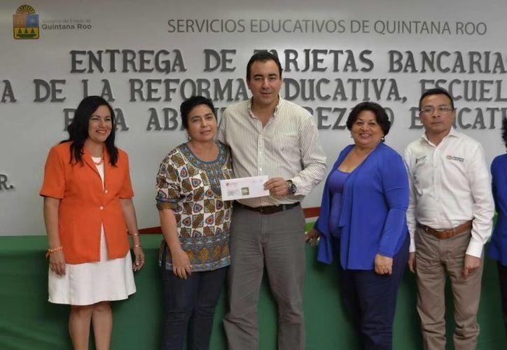 El titular de la SEyC, José Alberto Alonso Ovando, entregó las tarjetas bancarias con 50 mil pesos para cada ecuela beneficiada. (Cortesía)