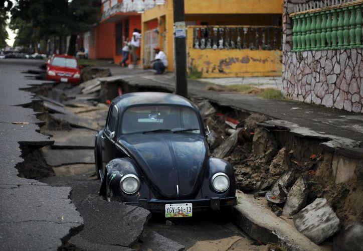 Un par de autos yacen en una porción de una calle hundida por las intensas lluvias en el puerto de Veracruz. (Agencias)