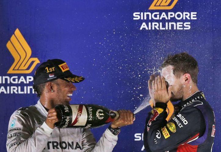 Como si fueran viejos amigos, el piloto inglés Lewis Hamilton (i) arroja sidra sobre el alemán Nico Rosbeg para celebrar la carrera de Fórmula Uno en Singapur, en la que el primero terminó en primer sitio para apoderarse del liderato del campeonato. (Foto: AP)