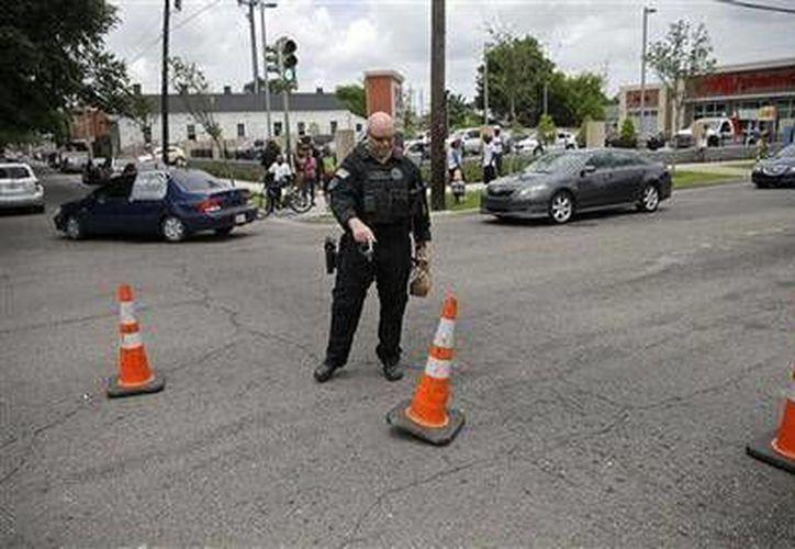 Un policía desvía el tránsito en el lugar donde un policía de Nueva Orleans fue muerto a tiros cuando transportaba a un prisionero. (Agencias)