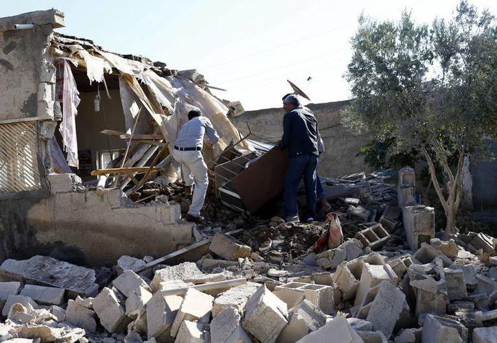 Dos hombres revisan entre los escombros de un edificio tras un ataque con mortero en Alanyurt, Siria, tras un ataque contra el Estado Islámico. (EFE)