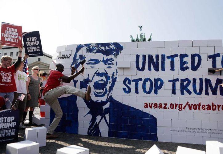 La campaña a votar contra Donald Trump se replica en varios países. En la imagen, un grupo de personas manifiesta su repudio al candidato republicano, en la Puerta de Brandenburgo, en Berlín, Alemania, el 23 de septiembre de 2016. (Foto: AP/Markus Schreiber)
