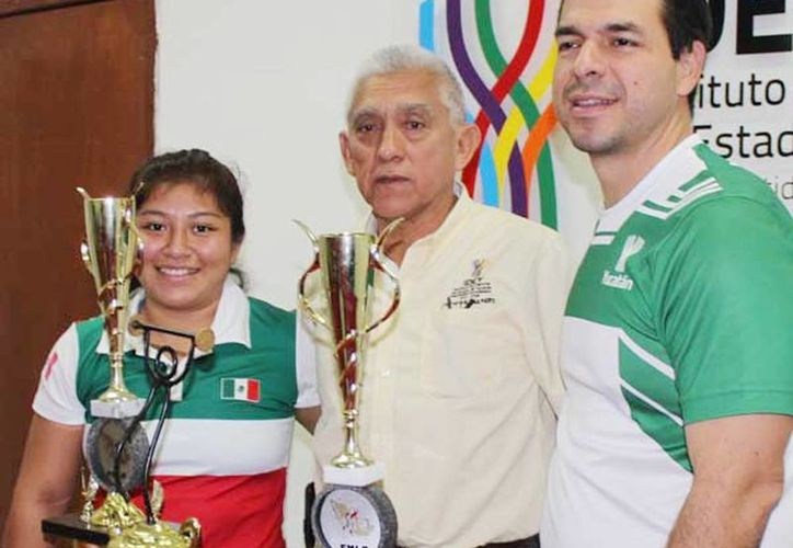 En la foto, la pesista seleccionada Mayra Couoh Azueta, Juan Sosa Puerto, director del Instituto del Deporte y David Carrillo Baranda, presidente de la asociación estatal del deporte de las pesas. (Milenio Novedades)