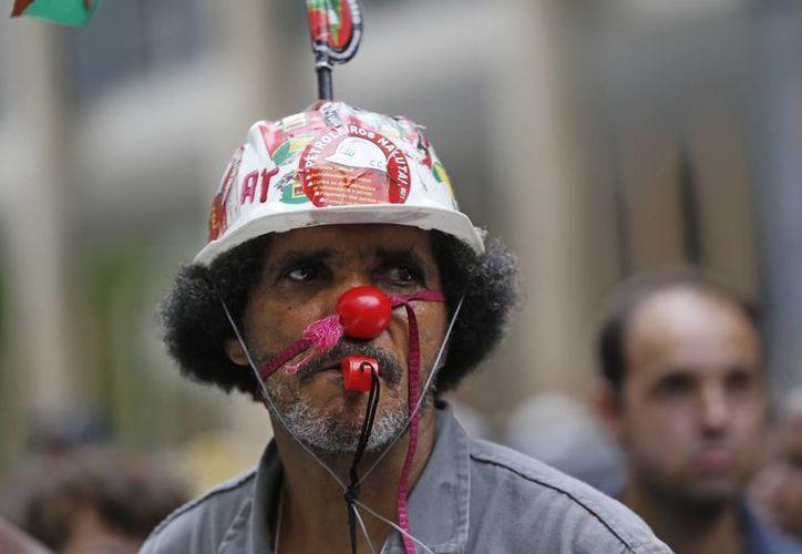 Un trabajador marcha durante una protesta por la corrupción que consideran envuelve el no pago que les correspondía, en Río de Janerio, Brasil. (Agencias)