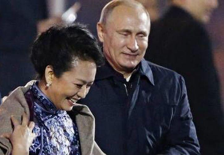 El presidente Rusia Vladimir Putin coloca un chal sobre los hombros de la esposa del presidente chino, en la cumbre de la APEC. (AP)