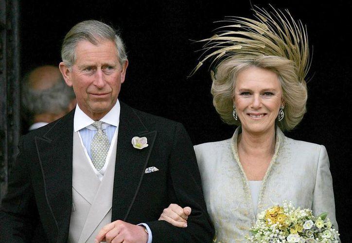 Imagen tomada el 9 de abril de 2005, del príncipe Carlos de Inglaterra y su esposa Camila, duquesa de Cornualles, a la salida de la capilla de San Jorge en Windsor, Inglatera, tras la bendición religiosa de su enlace civil. (Foto AP/ Alastair Grant, archivo)