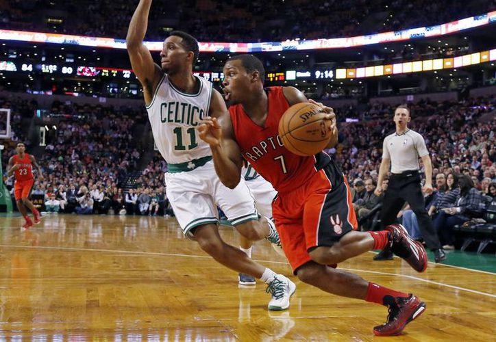 El guardia de Raptors, Kyle Lowry (7), conduce la pelota pese al acoso de Evan Turner, de Celtics, durante la segunda mitad del partido de la NBA. (Foto: AP)