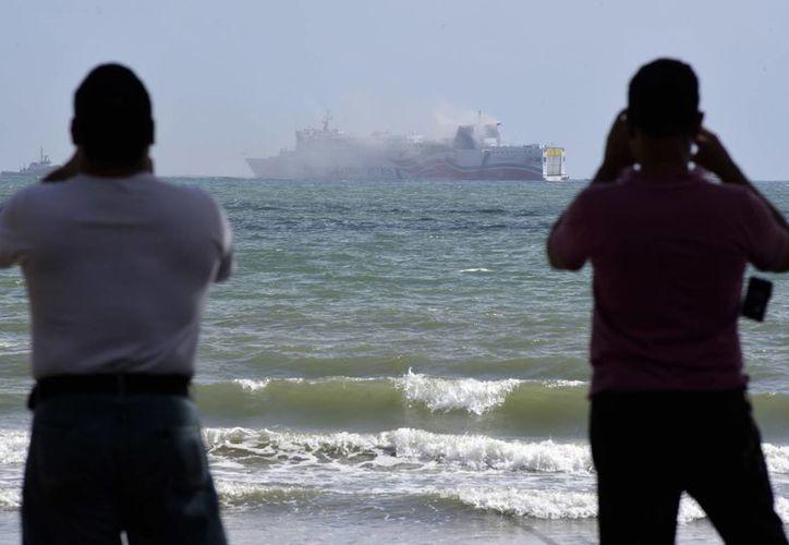 Dos hombres toman fotos con sus celulares al crucero Caribbean Fantasy, del cual sale humo por el incendio en el compartimiento de las turbinas, y el cual se propagó a otros sectores de la embarcación. (AP/Carlos Giusti)