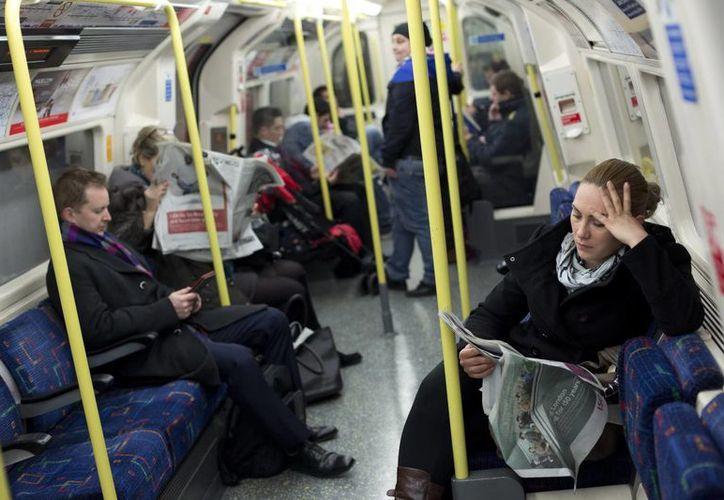 Una mujer lee un periódico mientras viaja en un vagón del metro de Londres, en Reino Unido. (Archivo/EFE)