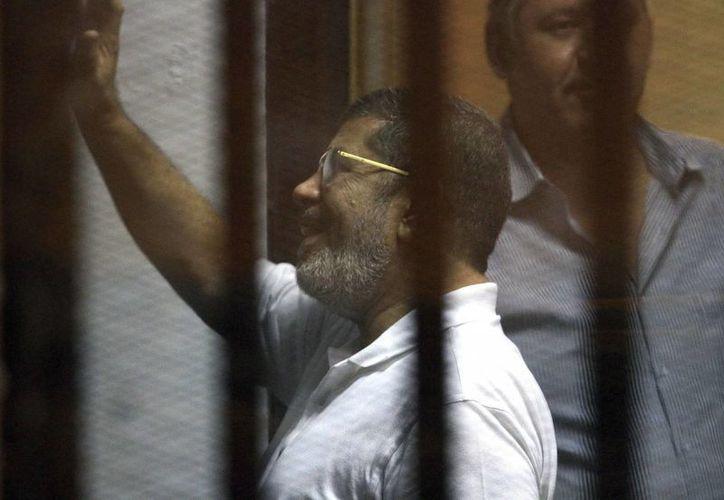 El expresidente depuesto de Egipto Mohamed Mursi (i) saluda a su llegada a una sesión del juicio al que fue sometido en El Cairo, Egipto, el pasado mes de agosto. (Archivo/EFE)