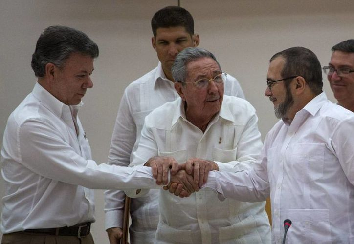 'Timochenko', de las FARC, y el presidente de Colombia se dan la mano tras anunciar el acuerdo que pondrá fin a 50 años de conflicto en ese país. Atestigua el presidente de Cuba, Raúl Castro. (AP)