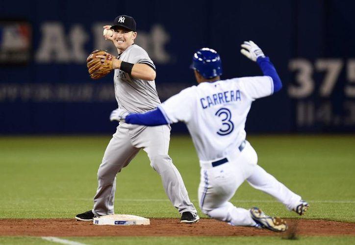 Stephen Drew, de Yanquis, lanza a primera base frente a Ezequiel Carrera (3), de Azulejos, que perdieron. (Foto: AP)
