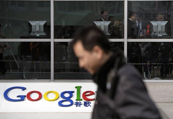 En la imagen de 2013 un guardia de seguridad pasa frente a varios extranjeros en la sede de Google en Beijing. China. El acceso a al servicio de correo electrónico de Google Inc. en China fue sido cortado. (Agencias)