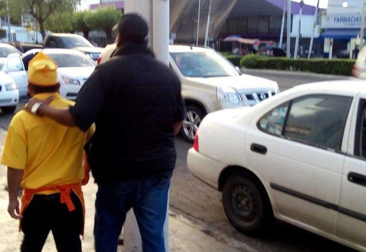 Imagen del momento en que uno de los empleados de la taquería 'La Guelaguetza' es detenido por las autoridades. (@fiscaliaqro)