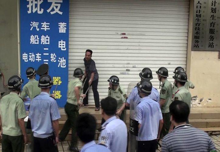 El personal de seguridad de China trata de someter a un hombre que ondea un machete afuera de la oficina de planeación familiar en la ciudad de Dongxing. (Agencias)