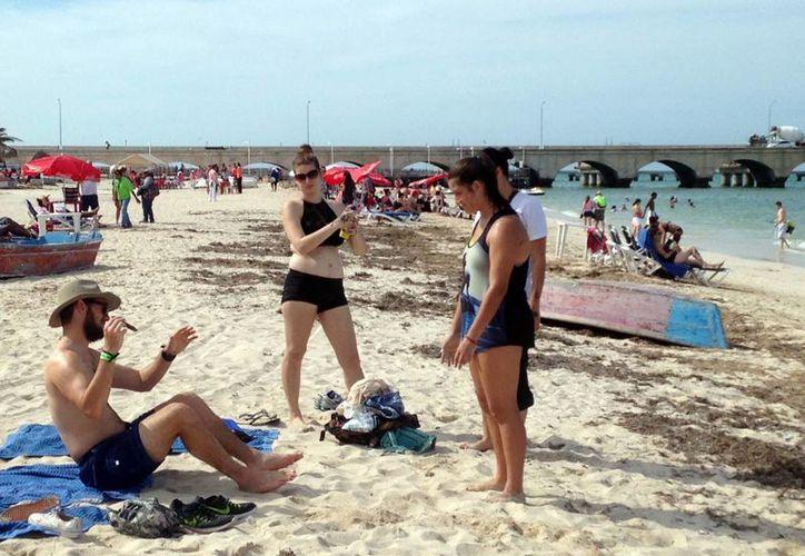 La economía del puerto, en problemas por los tours al interior del Estado. Imagen de un grupo de cruceristas en la playa de Progreso. (Milenio Novedades)