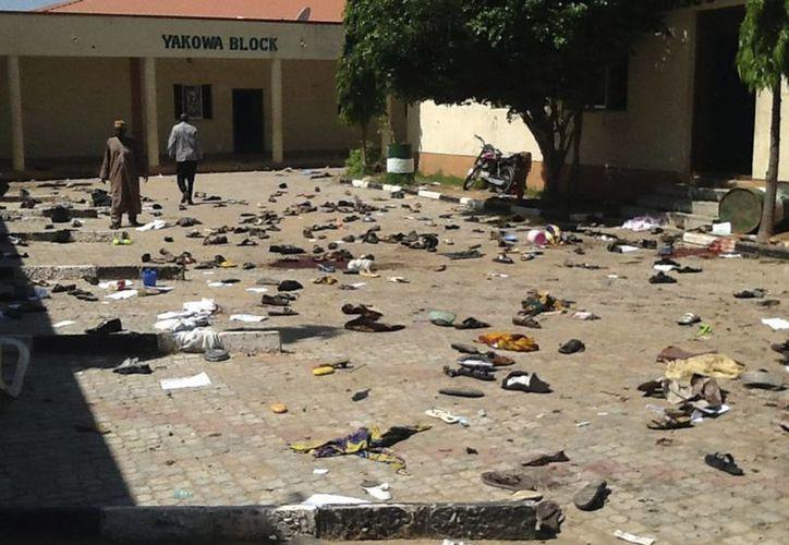 Agentes de seguridad nigerianos y miembros de la Cruz Roja, inspeccionan la zona donde explosionó un atentado bomba en Zaria, al norte de Nigeria. (Archivo/EFE)