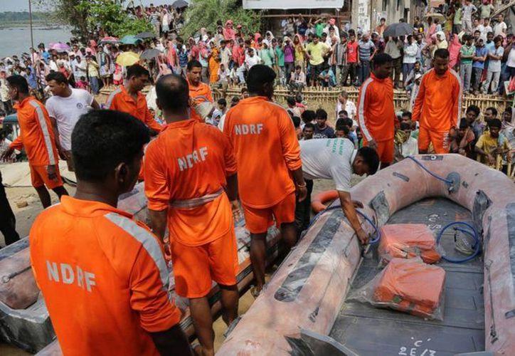 Equipos de rescate preparan sus barcos para buscar en el río Hooghly el bote que se hundió. (Agencias)