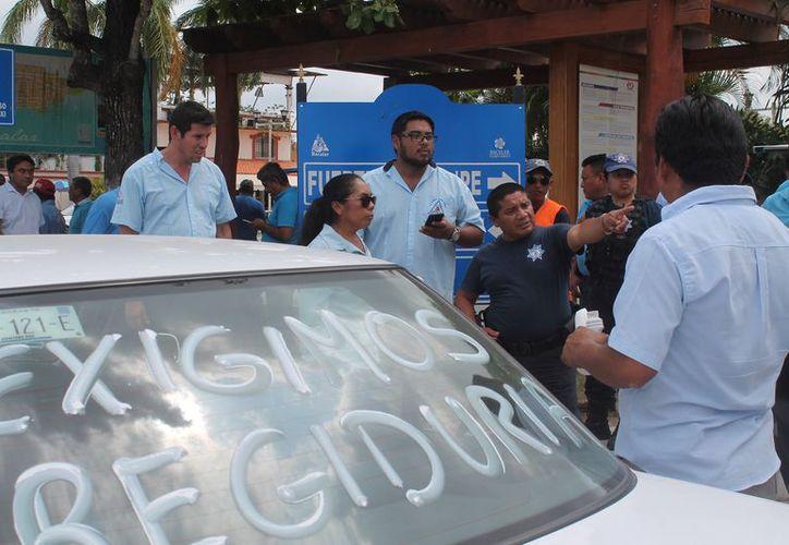 Los taxistas estuvieron afuera de las oficinas de las oficinas del PRI, y posteriormente se trasladaron frente al Palacio Municipal, donde se mantuvieron por más de una hora. (Javier Ortiz/SIPSE)
