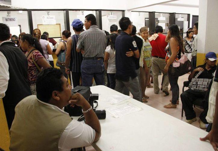 Algunos fotógrafos se distribuyen en los registros civiles para conseguir clientes. (Tomás Álvarez/SIPSE)