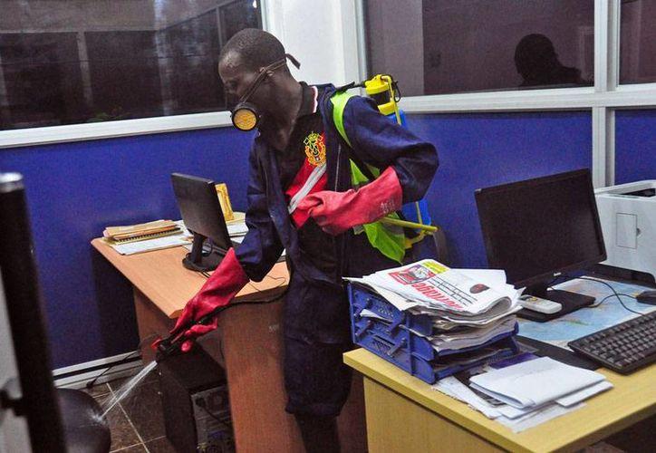 Una empleado desinfecta las oficinas públicas de Monrovia, capital de Liberia, en un día de asueto obligado, decretado por el Gobierno que busca intentar el contagio del ébola. De acuerdo con la OMS, la epidemia está fuera de control. (AP)