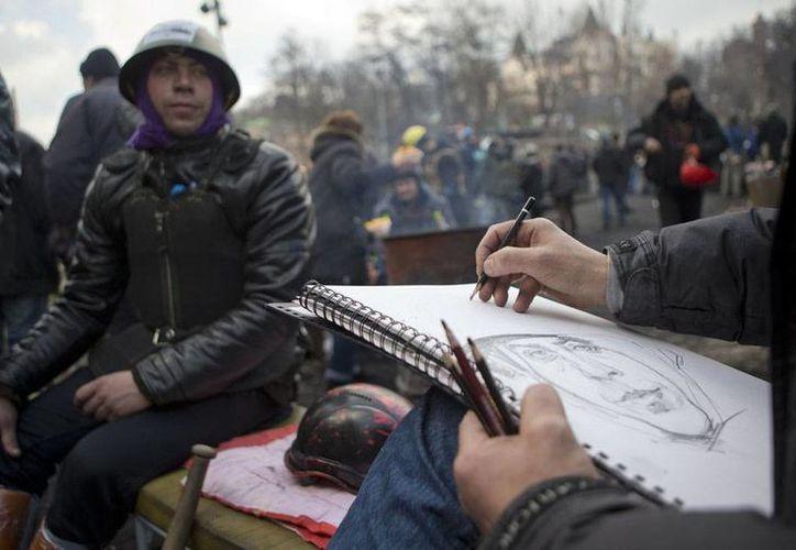 El Gobierno y la oposición firmaron un acuerdo para adelantar las elecciones en Ucrania; sin embargo, los manifestantes aún permanecen en las calles. En la imagen, ciudadanos opositores al régimen se toman 'un descanso' en una barricada, en Kiev. (Agencias)