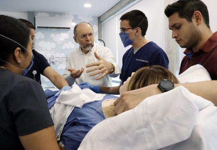 El Dr. Gumersindo Vázquez, docente de la Universidad Marista, da indicaciones a pasantes en un parto simulado. (José Acosta/ Milenio Novedades)