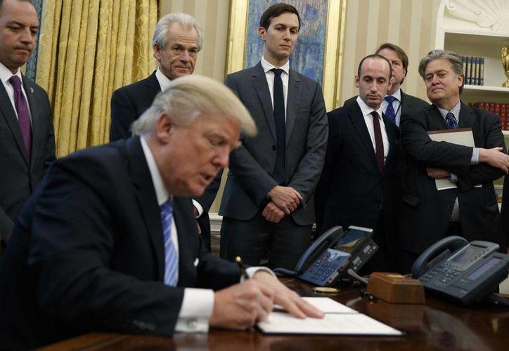 Momento en que Donald Trump firma la orden para que EU salga del TPP, el lunes 23 de enero de 2017. (AP/Evan Vucci)