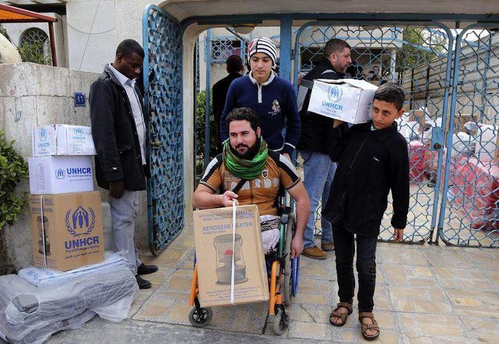 Iraquíes desplazados por el avance del Estado Islámico reciben ayuda humanitaria de la Agencia de ACNUR de la ONU, en Mansour, distrito de Bagdad. (Foto: AP/Karim Kadim)