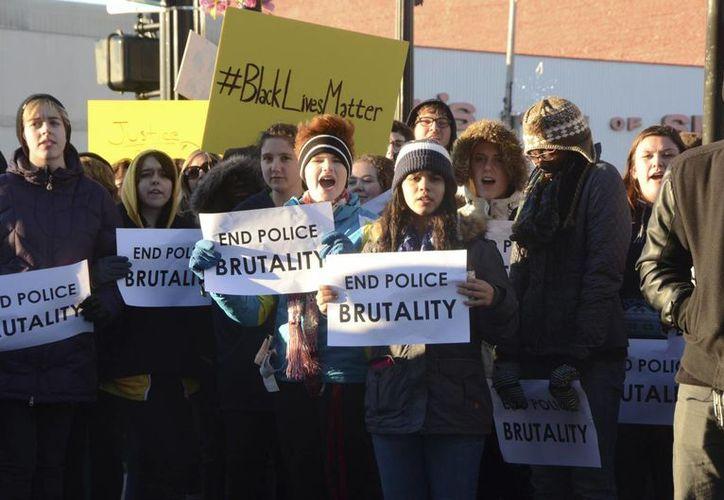 Cientos de personas con pancartas se manifiestan por las recientes decisiones del Gran Jurado en relación con los asesinatos de Michael Brown y Eric Garner en EU. (Agencias)
