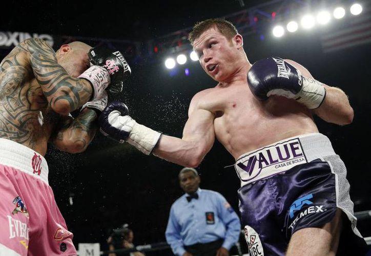 En los primeros asaltos se vio dominante Miguel Cotto, sin embargo, Saúl 'El Canelo' logró mejores golpes y gano la contienda por decisión unánime. (Foto AP)