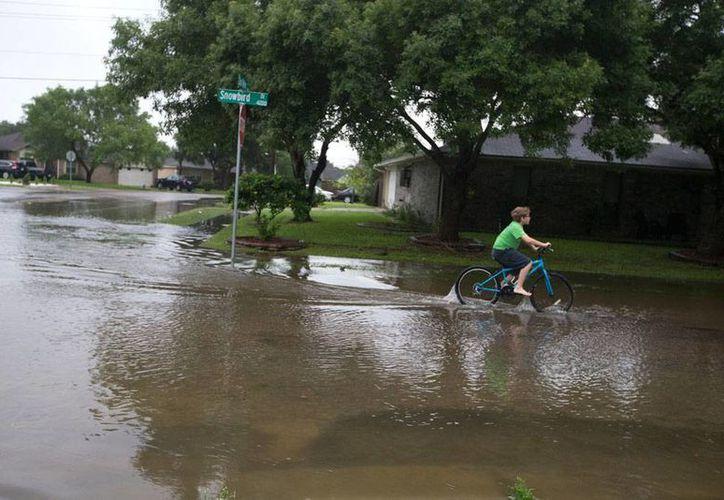 Owen Thornburgh, de 11 años, juega en el agua son su bicicleta, en una calle anegada de Corpus Christi, Texas. (Foto: Rachel Denny Clow/Corpus Christi Caller-Times via AP)
