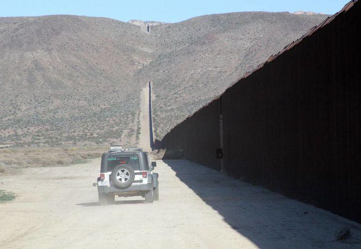 Un vehículo de la Patrulla Fronteriza vigila el muro fronterizo frente a las montañas de Jacumba, California, donde los inmigrantes aprovechan los huecos en la barrera para cruzar hacia EU. Una encuesta reveló que la mayoría de estadounidenses está en contra de la construcción de un nuevo muro, como propone Donald Trump. (EFE/Archivo)