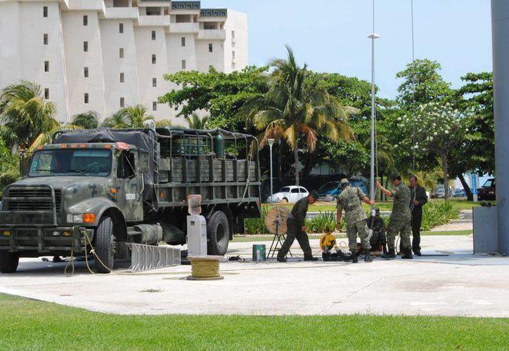 Dos camiones y una Hummer, con al menos 10 soldados, se postraron en el asta bandera de Cancún. (Jesús Tijerina/SIPSE)
