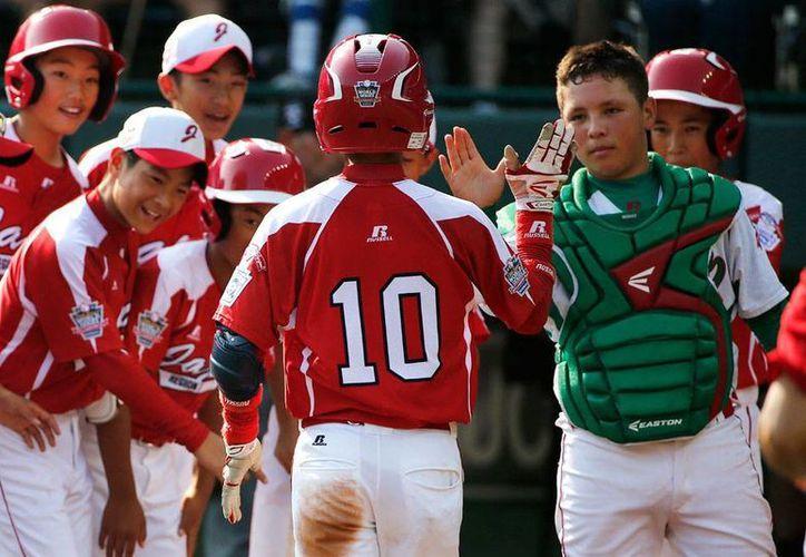 Hasta el catcher mexicano Juan Garza 'se rindió ante el japonés Suguru Kanamori, quien, en la imagen, llega a home tras conectar el palo de vuelta entera que selló el 'nócaut' contra México. (AP)