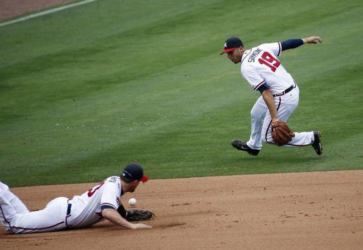 Una pelota se le escapa a Mike Zunino (3), el tercera base Chris Johnson (23) y el campocorto Andrelton Simmons (19), de Bravos de Atlanta, en el partido contra Marineros de Seattle. (Foto: AP)