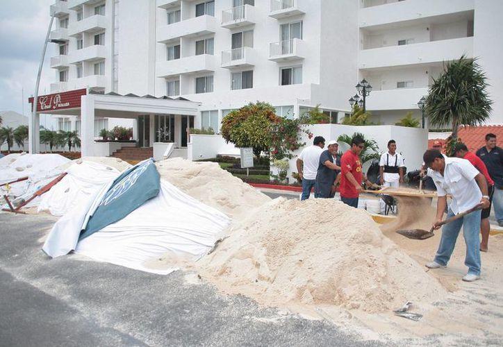 Extienden la arena entregada a uno de los hoteles beneficiados. (Julián Miranda/SIPSE)
